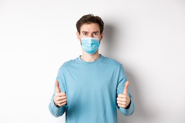 Covid-19、パンデミックおよび社会的距離の概念。カジュアルな服装と医療用マスクを身に着けた若い男性。親指を立てて真剣に見え、検疫中にウイルスから保護します。