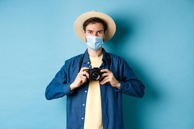 Covid-19, концепция пандемии и путешествий. веселый турист в летней шляпе и медицинской маске фотографирует, держа камеру, стоя на синем фоне.
