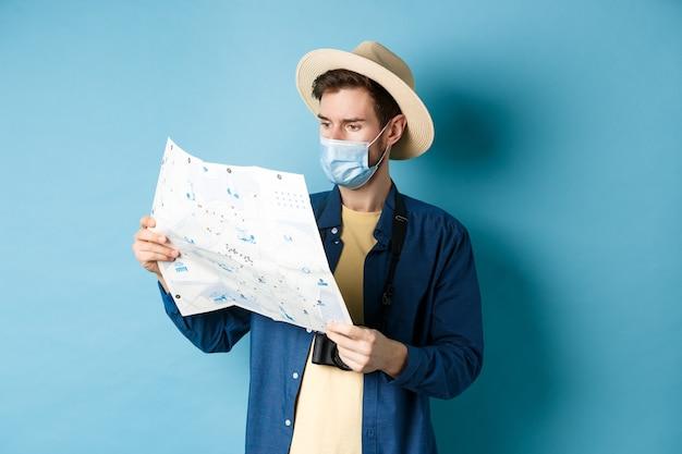 Covid-19, концепция пандемии и путешествий. красивый молодой парень в маске и летней шляпе, глядя на туристическую карту, путешествуя в отпуске, стоя на синем фоне.