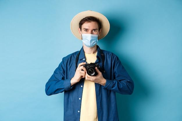 Covid-19, концепция пандемии и путешествий. счастливый парень в отпуске фотографирует с камерой, в медицинской маске и летней шляпе, на синем фоне.