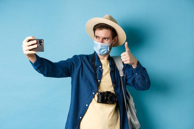 Covid-19、パンデミックおよび旅行の概念。休暇中に写真を撮る幸せな男性の観光客は、親指を立てて、ホテルをお勧めし、青い背景の上に立って自分撮りをします。