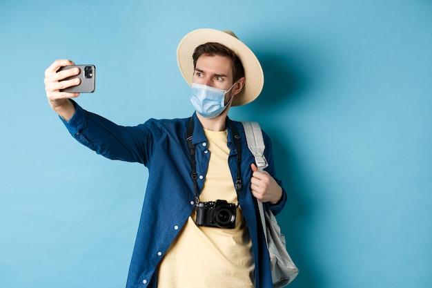 Covid-19、パンデミックおよび旅行の概念。夏休みの観光客は、医療マスクで自分撮りを取り、スマートフォンで写真を撮る、青い背景の上に立っています。
