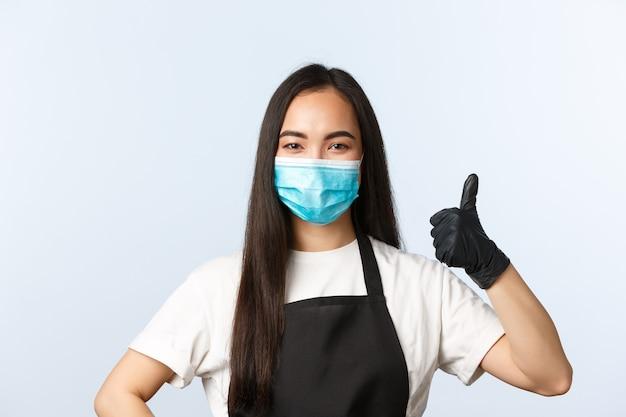 Covid-19パンデミック、コーヒーショップ、中小企業、ウイルス予防の概念。陽気な明るい笑顔のアジアの女性バリスタ、医療マスクと手袋のウェイトレスは親指を表示します