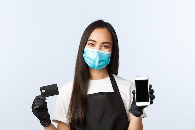 Covid-19パンデミック、コーヒーショップ、中小企業、ウイルス予防の概念。笑顔の楽しいアジアの女性労働者、医療マスクショースマートフォンとクレジットカードのカフェバリスタ