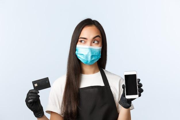 Covid-19パンデミック、コーヒーショップ、中小企業、ウイルスの概念。思いやりのある若いアジアの女性バリスタ、医療マスク思考のウェイトレス、クレジットカードを保持し、携帯電話のディスプレイを表示