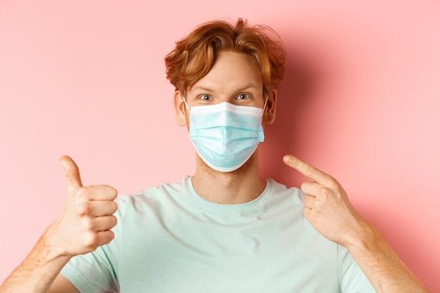 Covid-19 e concetto di pandemia. bel ragazzo dai capelli rossi che punta il dito sulla maschera facciale e mostra il pollice in su, usando le misure del coronavirus, in piedi su sfondo rosa.