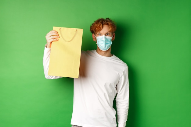 Covid-19 and pandemic concept. surprised man in face mask showing shopping bag and looking at camera, standing over green background.