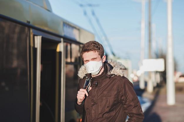 Covid-19パンデミックコロナウイルスは公共の場所にいる人。若い男が防護マスクを着用しています。コロナウイルス保護
