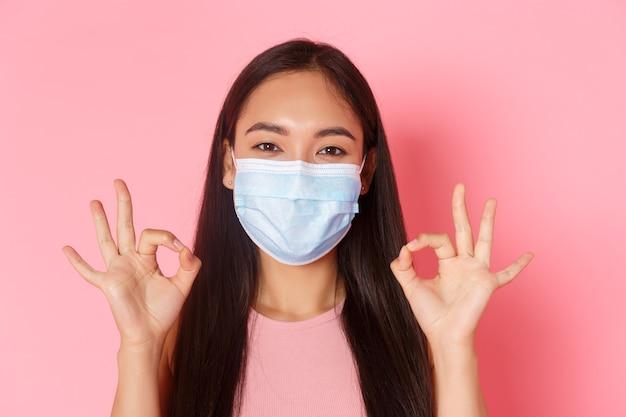 Пандемия covid-19, коронавирус и концепция социального дистанцирования. крупным планом взволнованная и пораженная симпатичная азиатская девушка хвалит отличный выбор, хорошо выполненную или хорошую работу жестом, показывает все в порядке и надевает медицинскую маску