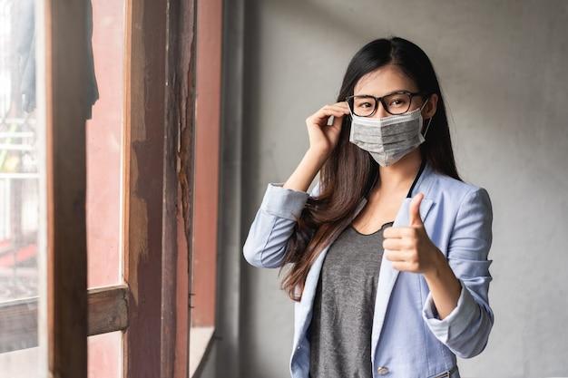 Covid-19パンデミックコロナウイルス、アジアの女性は風邪をひいており、咳、発熱、頭痛、痛みの症状があります