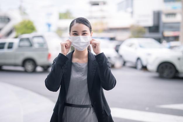 Covid-19流行ウイルスsars-cov-2の拡散を防ぐフェイスマスクを身に着けている都市通りのパンデミックコロナウイルスアジア人女性。コロナウイルス病2019に対して顔に防護マスクを持つ少女。