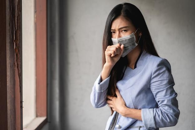Covid-19パンデミックコロナウイルス、マスクを身に着けているアジアの女性、咳と発熱の症状があります