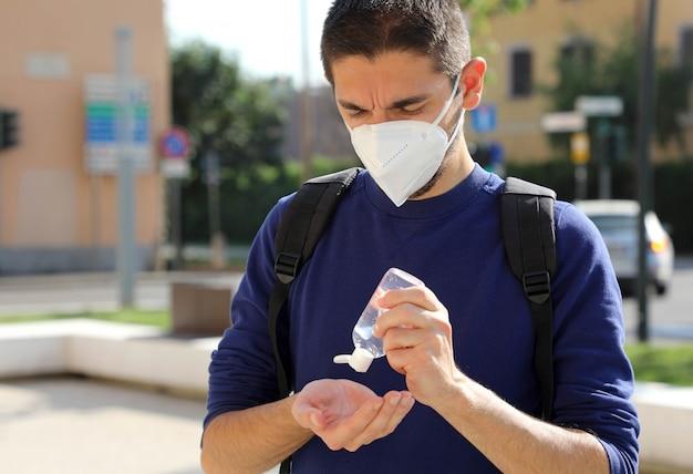 Covid-19パンデミックコロナウイルスシティストリートでアルコールゲル消毒剤の手を使用してffp2マスクを持つ男をクローズアップ。