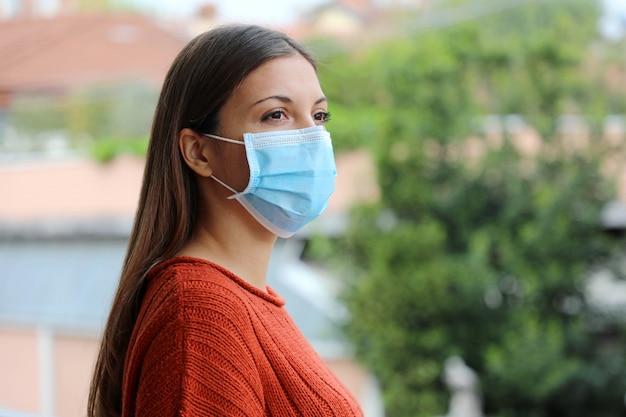 Covid-19パンデミックコロナウイルスクローズアップ女性隔離された家検疫バルコニーテラスコロナウイルス病に対する外科用マスク2019。