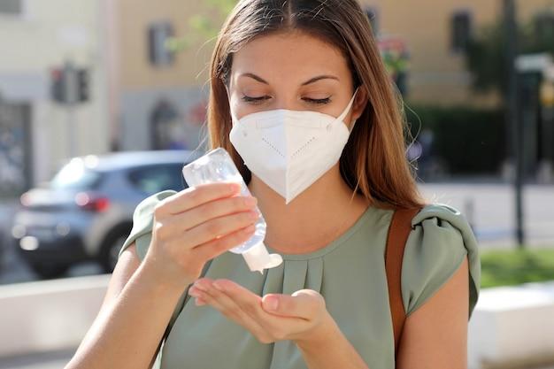 Пандемия коронавируса covid-19 крупным планом женщина с маской ffp2, использующая дезинфицирующее средство со спиртовым гелем, на городской улице.