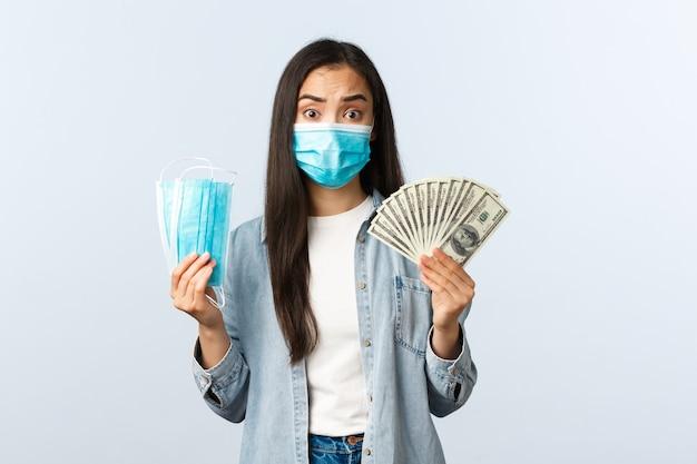코비드-19 전염병, 코로나바이러스 비용 및 금융 개념. 걱정스럽고 복잡한 고민에 빠진 아시아 소녀는 비싸고 인공 호흡기를 살 여유가 없는 의료용 마스크에 많은 돈을 지불합니다.