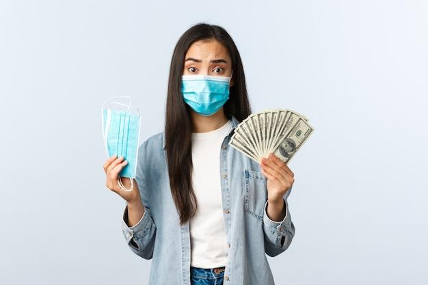 코비드-19 전염병, 코로나바이러스 비용 및 금융 개념. 걱정스럽고 복잡한 고통받는 아시아 소녀는 비싼 의료용 마스크에 많은 돈을 지불합니다