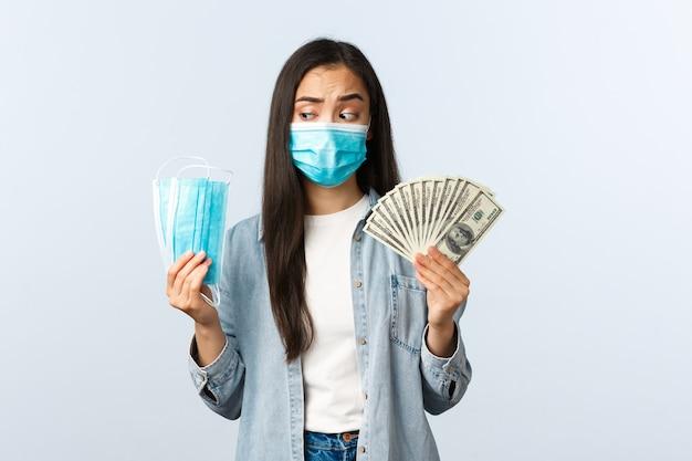 코비드-19 전염병, 코로나바이러스 비용 및 금융 개념. 사려 깊고 어리둥절한 아시아 여성이 의료용 마스크를 보고 돈을 보여주고 코로나바이러스 동안 돈을 잃는다