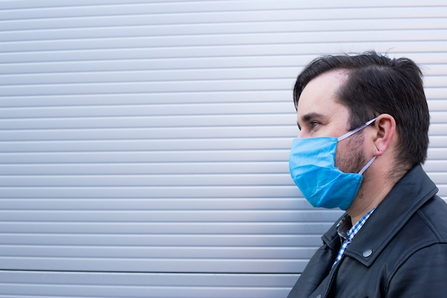 Covid-19コロナウイルス病2019の拡大を防ぐフェイスマスクを身に着けている都市通りのパンデミックコロナウイルス男。sars-cov-2に対して顔にサージカルマスクを付けた男の肖像