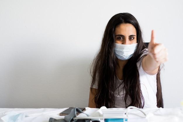Covid-19パンデミックコロナウイルスマスク女性看護師病院またはウイルスsars-cov-2の自宅隔離自動検疫。女の子の自発的隔離サージカルマスク。勝利の合図。病気2019。