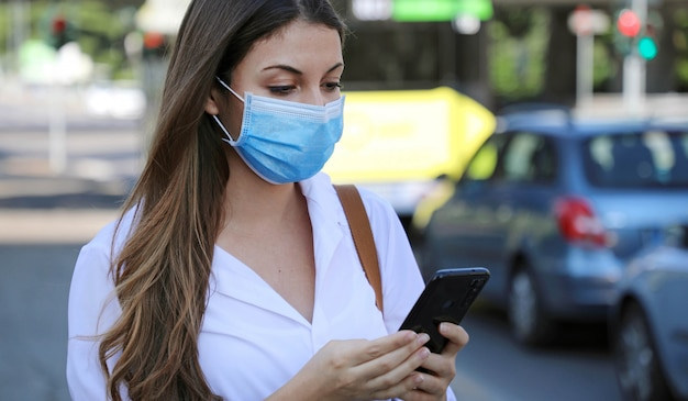 Covid-19 pandemic coronavirus mobile application -young woman wearing surgical mask using smart phone app in city street