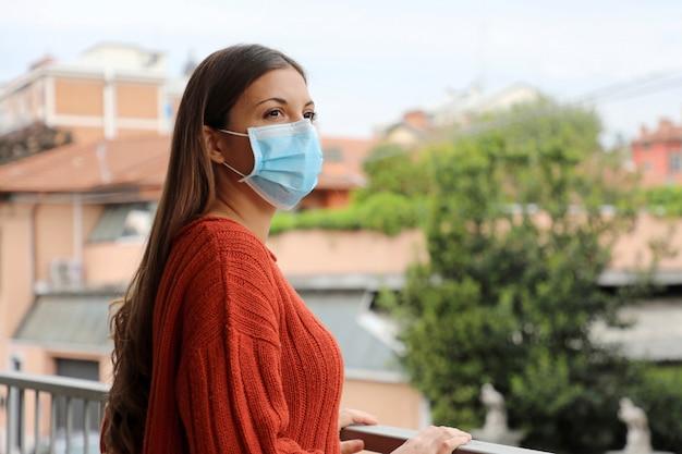 Covid-19コロナウイルス病に対するパンデミックコロナウイルス女性隔離家検疫バルコニーテラス外科マスク2019。