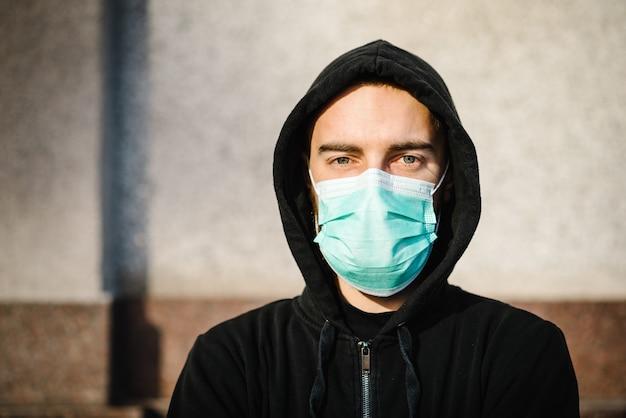 Covid-19パンデミックコロナウイルス。病気の拡大を防ぐフェイスマスクを身に着けている街の通りの若い男covid-19。 sars-cov-2に対して顔にサージカルマスクを持つ男のクローズアップ。