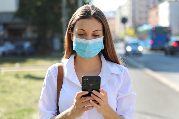 Covid-19 pandemic coronavirusyoung woman wearing surgical mask using smart phone app in city street