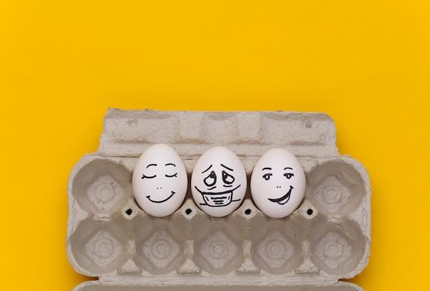 코로나 19 감염병 세계적 유행. 노란색 배경에 얼굴로 계란이 있는 계란 트레이. 평면도