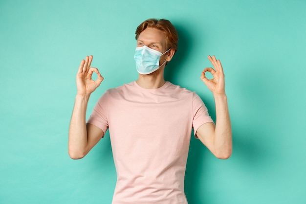 Covid-19, pandemic and lifestyle concept. cheerful redhead man in medical mask showing okay signs in approval, like and praise product, looking left at copy space.