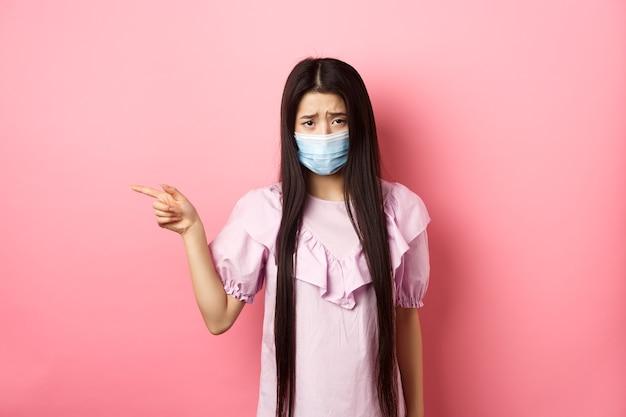 Covid-19、パンデミックライフスタイルのコンセプト。左を指している医療マスクの悲しくて暗いアジアの女の子は、ピンクの背景に失望して立って、不公平な状況に不平を言います。