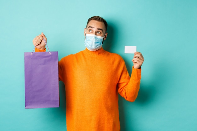 Covid-19, pandemic and lifestyle concept. thoughtful man in face mask, holding purple shopping bag and credit card, thinking or imaging, standing over turquoise background.