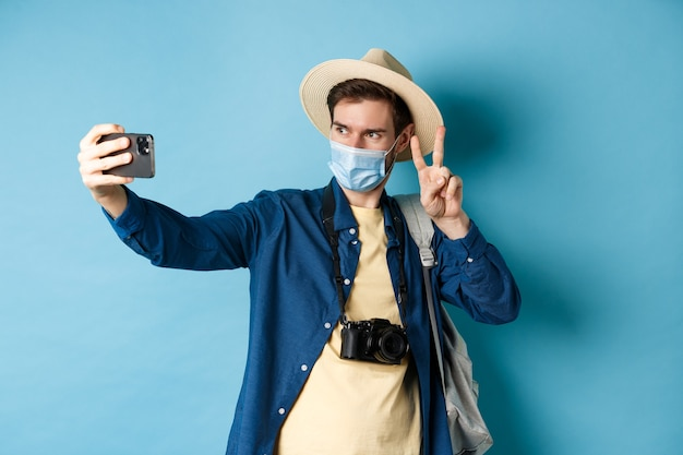 Covid-19, pandemic and travel concept. happy and positive guy in tourist hat taking selfie and showing peace sign, posing near sightseeing, blue background.