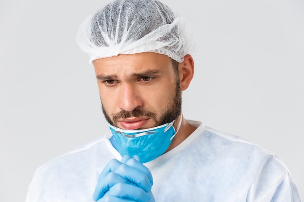Covid-19パンデミック、ウイルスの発生、診療所および医療従事者の概念。神がコロナウイルスワクチンを見つけて、呼吸器なしで懇願することを祈って、信仰を持っている絶望的な心配している医者のクローズアップショット。
