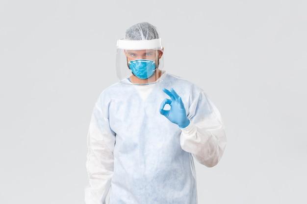 Covid-19パンデミック、ウイルスの発生、診療所および医療従事者の概念。個人用保護具に自信を持っている真面目な医師は、大丈夫な兆候を示し、患者を警戒することを保証します。