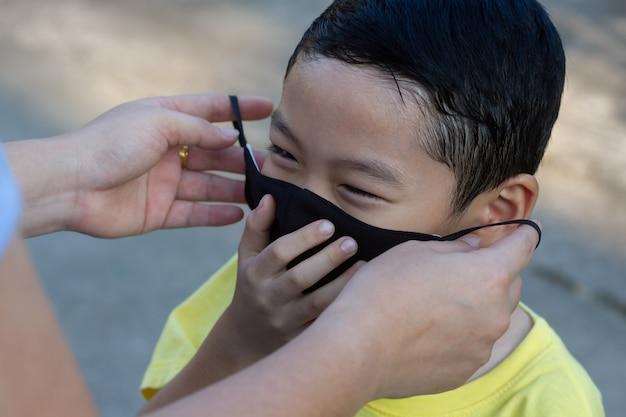 彼女の息子に暗い色の防護マスクを着ているお母さん。笑顔の黒い髪のアジアの少年は母親がフェイスマスクを着用します。 covid-19ヘルスケアまたはpm 2.5マイクロダスト汚染問題概念の背景。