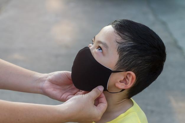 彼女の息子のために暗い色の防護マスクを身に着けているママ。黒髪のアジアの少年は母親と一緒に黒いフェイスマスクを着用しています。 covid-19ヘルスケアまたはpm 2.5マイクロダスト汚染問題概念の背景。