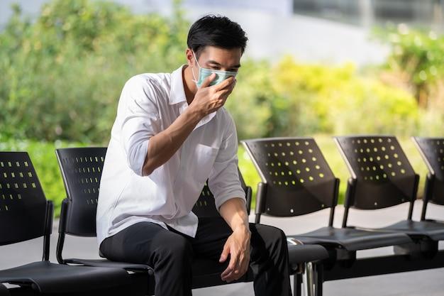 Молодой азиатский человек носит медицинскую маску для защиты от коронавируса, covid-19 и pm2.5 в городском городе