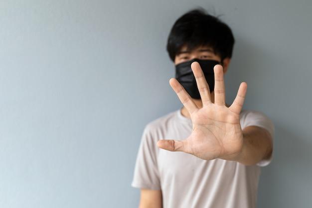 Крупным планом мужчины в маске для защиты от коронавируса (covid-19) и пыли pm2.5 с изображением ладони рук