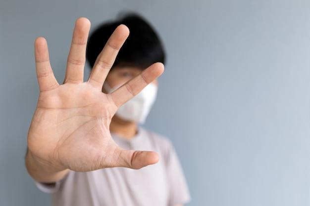 手のひらを見せてコロナウイルス(covid-19)とpm2.5のほこりを保護するマスクを身に着けているクローズアップの男性