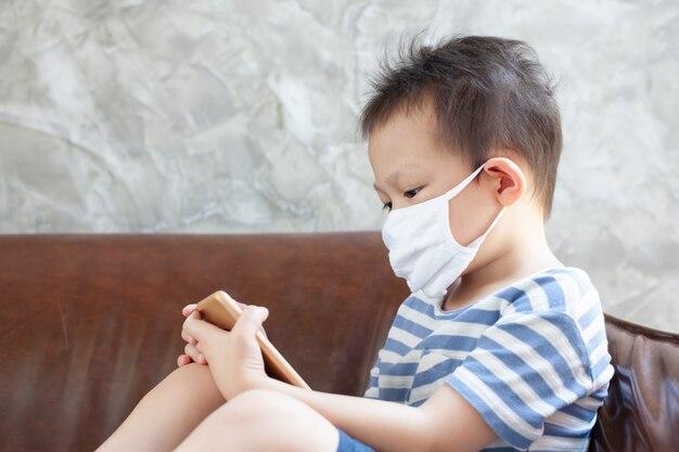 保護マスクを身に着けているアジアの子供男の子は、コロナウイルスcovid-19と大気汚染pm2.5から自宅のスマートフォンで検疫しています。