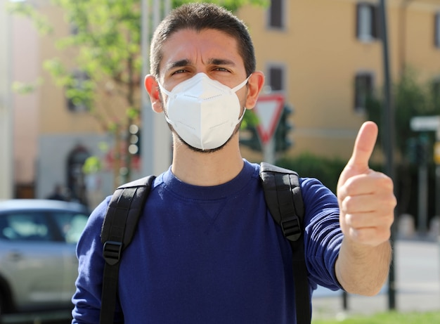 Covid-19 positive young man wearing protective mask  ffp2 avoiding coronavirus disease 2019 showing thumbs up in city street