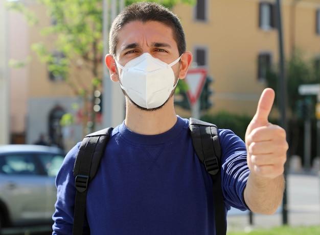 Covid-19ポジティブな若者が防護マスクを着用ffp2がコロナウイルス病を回避2019街で親指を立てる