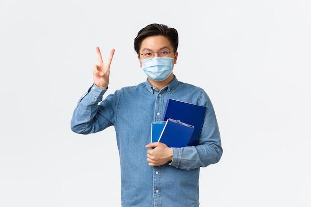 Covid-19, профилактика вирусов и социальное дистанцирование в университетской концепции. веселый и оптимистичный азиатский студент-мужчина в очках и медицинской маске, демонстрирующий мир, жест каваи, переносит ноутбуки.