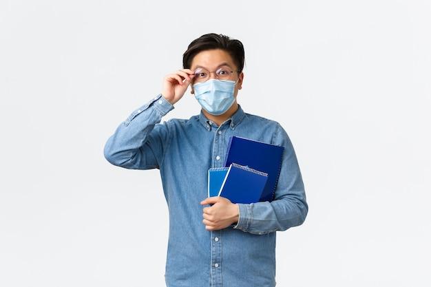 Covid-19, профилактика вирусов и социальное дистанцирование в университетской концепции. восторженный счастливый азиатский мужчина в медицинской маске стоит с ноутбуками и поправляет очки на носу, белый фон