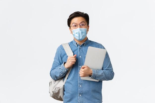 Covid-19, профилактика вирусов и социальное дистанцирование в университетской концепции. удивленный общительный азиатский парень, студент с рюкзаком и ноутбуком, заинтересованный в камеру, в медицинской маске и очках.