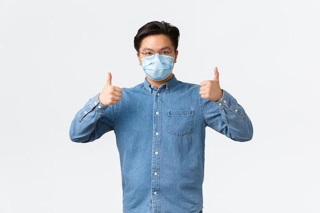 코비드-19, 바이러스 예방, 직장 개념에서의 사회적 거리. 셔츠와 의료용 마스크를 쓴 자신감 있는 아시아 남성이 엄지손가락을 위로 올려 코로나바이러스 동안 직원의 안전을 보장합니다.