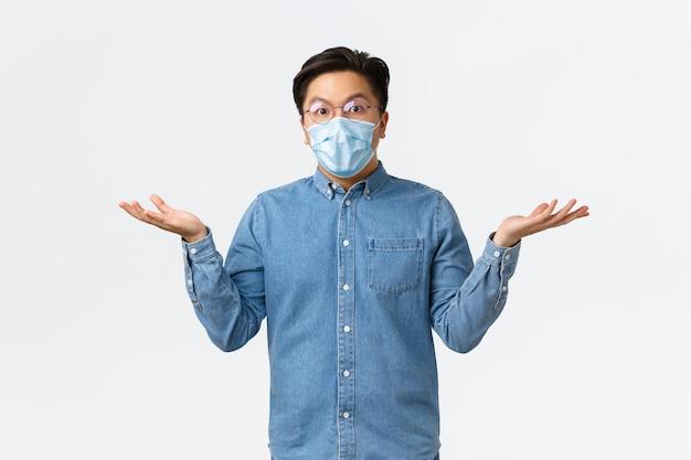 코비드-19, 바이러스 예방, 직장 개념에서의 사회적 거리. 혼란스럽고 놀란 아시아 남성 기업가는 손을 옆으로 펼치고 의아해 어깨를 으쓱하고 의료 마스크와 안경을 착용합니다.