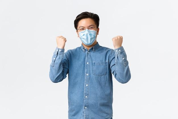 Covid-19, профилактика вируса и концепция социального дистанцирования на рабочем месте. успешный победивший азиатский мужчина призывает команду носить медицинские маски для борьбы с коронавирусом, торжествуя подняв руки вверх