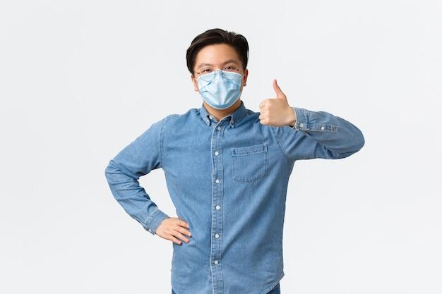 코비드-19, 바이러스 예방, 직장 개념에서의 사회적 거리. 의료용 마스크를 쓴 쾌활한 아시아 남성 기업가가 승인을 받고 팀워크를 칭찬하는 모습을 보여줍니다.
